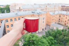 Rånar rött hållande kaffe för mannen utomhus Royaltyfri Foto