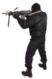 Rånare i svart likformig och maskering med maskingeväret Arkivfoto