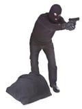 Rånare med säcken som siktar med hans vapen Arkivfoto