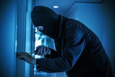 Rånare med svart strumpbyxor över huvudet som bryter dörrlåset Arkivbilder