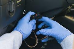 Rånaren i blåa handskar bryter lagen, stjäler en bil, genom att hacka in i säkerhetssystemet arkivfoto