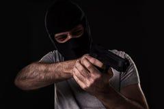 Rånaren i en maskering med ett vapen som pekas till sidan på en svart bakgrund royaltyfria foton