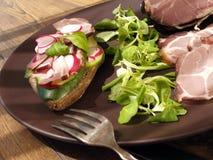 Råolja torkad saltad och rökt skinkaskinka med smörgåsen, sallad på plattan Royaltyfri Bild