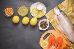 Rått bastant sådan rå fisk på hantverkpapper på gråa tabletop skivor för en citron för smaktillsats för citronpepparolja med salt royaltyfria foton