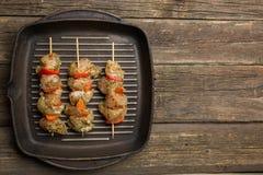 rått chiken kött med grönsaker på steknålar på gallergjutjärnpannan royaltyfria bilder