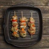 rått chiken kött med grönsaker på steknålar på gallergjutjärnpannan royaltyfria foton
