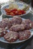 Rått griskött- och nötköttkött som förbereds för hamburgare på den vita rundade skärbrädan arkivfoto