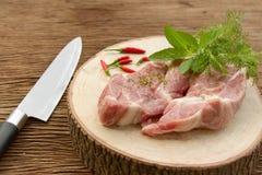 Rått griskött på skärbräda Royaltyfria Bilder