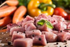 Rått griskött på skärbräda och nya grönsaker Arkivbilder