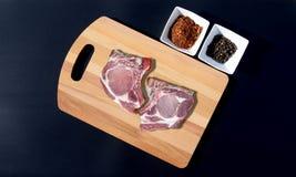 Rått grisköttkött på en skärbräda och en peppar Arkivfoton