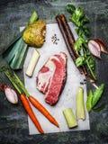 Rått kött för nötköttbringa med organiska grönsakingredienser för soppa- eller buljongmatlagning på lantlig bakgrund Royaltyfria Bilder