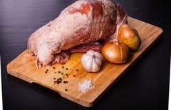 Rått kött, lök, vitlök och kryddor på ett träbräde tonat Royaltyfria Foton