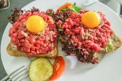 Rått kött med ägget på bröd Arkivfoto