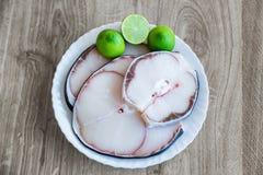 Rått kött och limefrukt för blå haj på den vita plattan arkivbild
