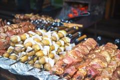 Rått kött och potatisar som är förberedda för att steka på steknålar Arkivbilder