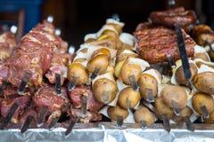 Rått kött och potatisar som är förberedda för att steka på steknålar Arkivbild