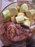 Rått kött och skivade zucchini och potatisar i en bunke Arkivfoton