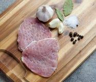 Rått kött på en träskärbräda med kryddor Arkivbild