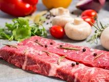 Rått kött på ett ark av tenn Närliggande kryddor, smaktillsatser och vegeta Royaltyfria Foton