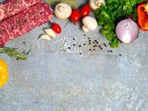 Rått kött på ett ark av tenn Närliggande kryddor, smaktillsatser och vegeta Fotografering för Bildbyråer
