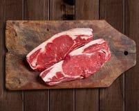Rått kött på trätabellen Arkivbilder