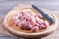 Rått kött tärnade med den kökkniven och skärbrädan arkivbild