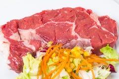 Rått kalvkött och sallad Arkivbild