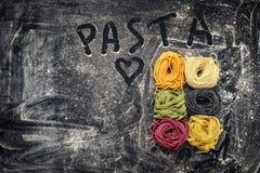 Rått kulört tagliatelle- och spagettirede på svart bakgrund arkivbild