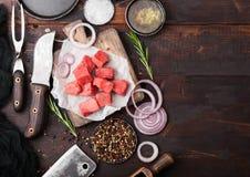 Rått luta tärnad biff för eldfast formnötköttgriskött med den tappningkötthandyxan och kniven och gaffeln på träbakgrund Salta oc fotografering för bildbyråer