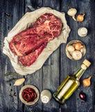 Rått marmorerat nötköttkött med ingrredients för att laga mat på lantlig träbakgrund, bästa sikt Royaltyfria Foton
