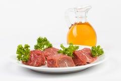 Rått nötkött på den vita plattan skaka oljeolivgrön Arkivbilder