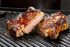 Rått nötkött på gallret Arkivbilder