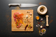 Rått nytt grisköttkött ombord med smaktillsatser på mörk bakgrund Arkivfoto