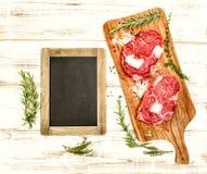 Rått nytt kött med örter, kryddor och svart tavla matbackgroun Arkivfoto