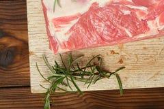 Rått skuldralamm på träbräde och tabellen Royaltyfri Fotografi