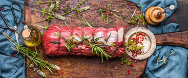 Rått steknötkött med örter som binds med ett rep med matlagningingredienser, olja och kryddor på lantlig bakgrund, bästa sikt arkivbilder