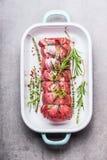 Rått steknötkött som binds med ett rep med örter, och kryddor som binds med ett rep i en vit emalj, bowlar royaltyfria bilder