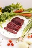 Rått strutskött för skiva med grönsaken Arkivbild