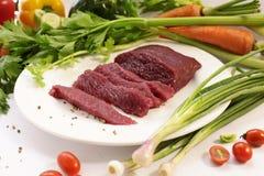 Rått strutskött för skiva med grönsaken Fotografering för Bildbyråer