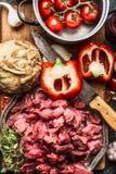 Rått tärnat nötköttkött, grönsakingrediensen, kökkniven och matlagning lägger in Ragu- eller gulaschförberedelse royaltyfri fotografi