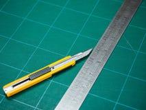 Règle de coupeur et de fer d'isolement sur un tapis de coupure images stock