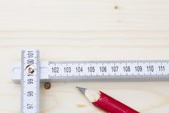 Règle rouge de crayon et de pliage se trouvant sur le conseil en bois Photographie stock libre de droits