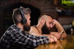 Réalité d'évasion Relaxation de vendredi dans la barre Homme barbu de hippie dépenser des loisirs au compteur de barre Boissons d photos stock