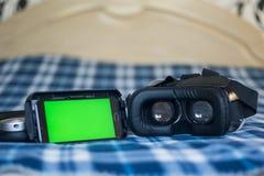 Réalité virtuelle, helmetбsmartphone de VR et écouteurs avec le vert Photographie stock