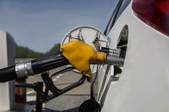 Réapprovisionnement en combustible à la station service Vieux pistolet jaune avec un tuyau dans le réservoir de gaz de la voiture photo stock