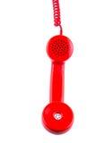 Récepteur téléphonique rouge sur le fond blanc. Image stock