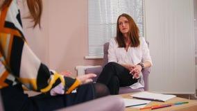 Réception au psychologue dans la clinique Le docteur écoutant les problèmes de clients banque de vidéos