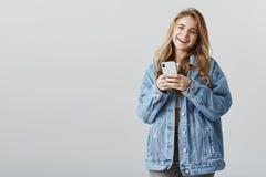 Réception des compliments au sujet de nouveau dispositif Amie amicale heureuse attirante dans la veste à la mode de denim, se ten Photos libres de droits