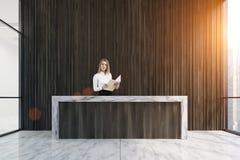 Réception en bois foncée et femme blonde Photo libre de droits