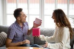 Réception enthousiaste de boîte-cadeau d'ouverture de jeune homme actuelle de l'épouse Image libre de droits